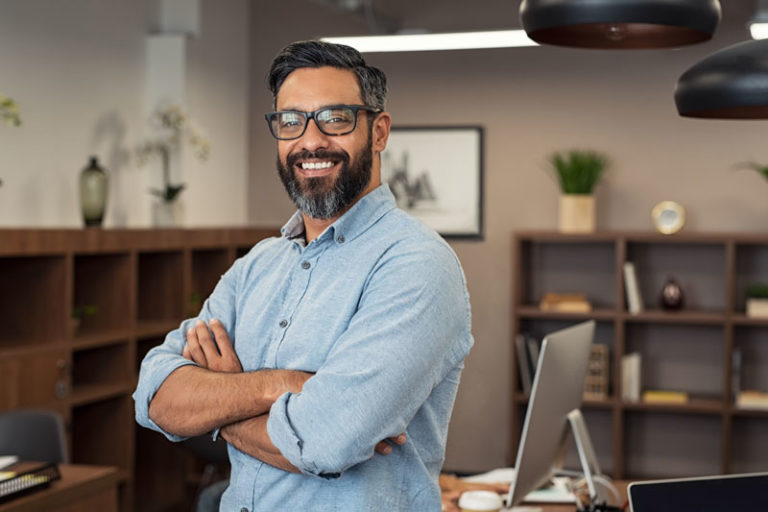Smiling man wearing glasses with arms folded standing in office