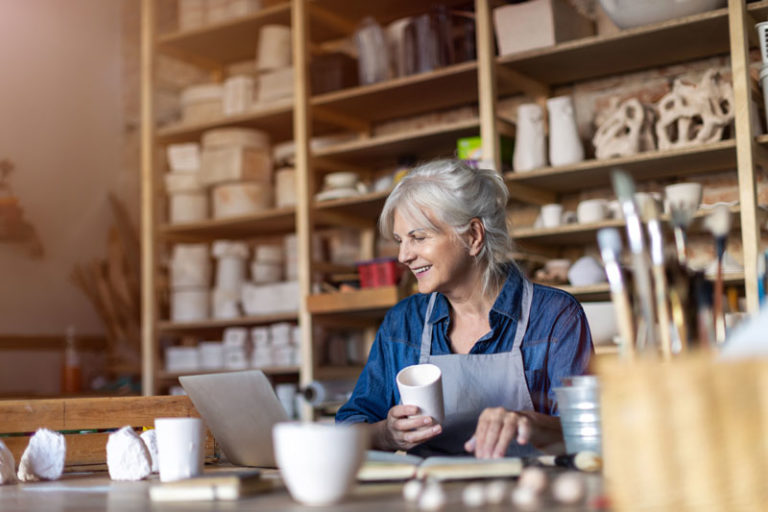 Smiling old woman in pottery room looking at a laptop