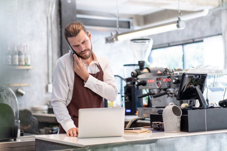 Male barista next to coffee machine and with computer in front of him frowning whilst on the phone