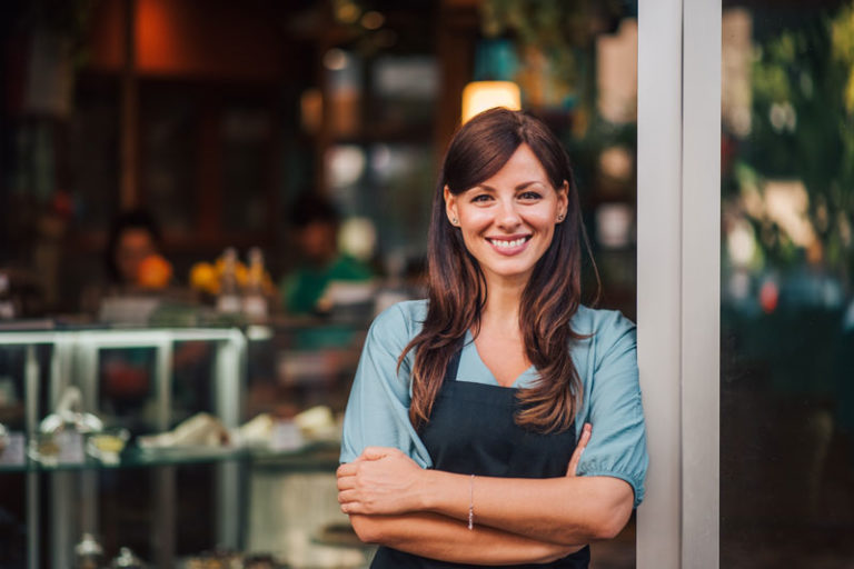 Mid-shot of standing female in apron smiling and folding her arms whilst leaning against the entry way to a store.