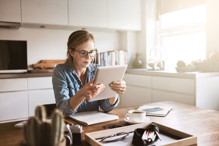 Woman seated at kitchen table holding tablet with documents around her