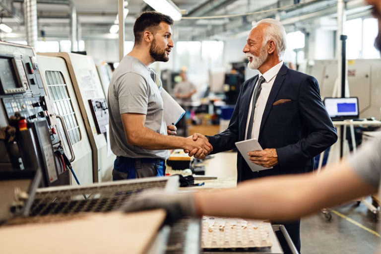 Business man shakes working man's hand in factory