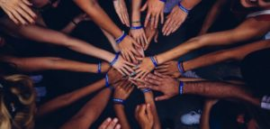 Overhead shot of group of people putting hands in the middle of a huddle